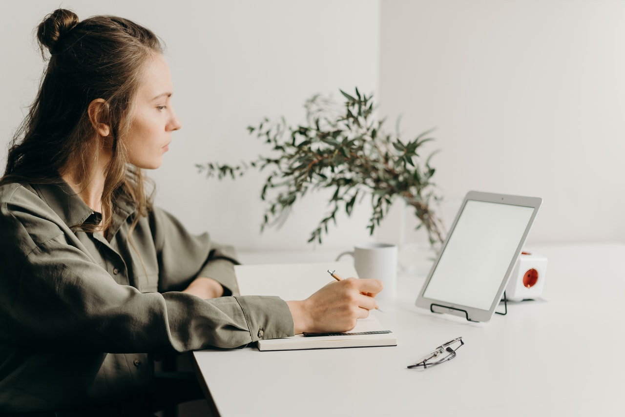 woman-in-gray-coat-using-white-laptop-computer-4065891